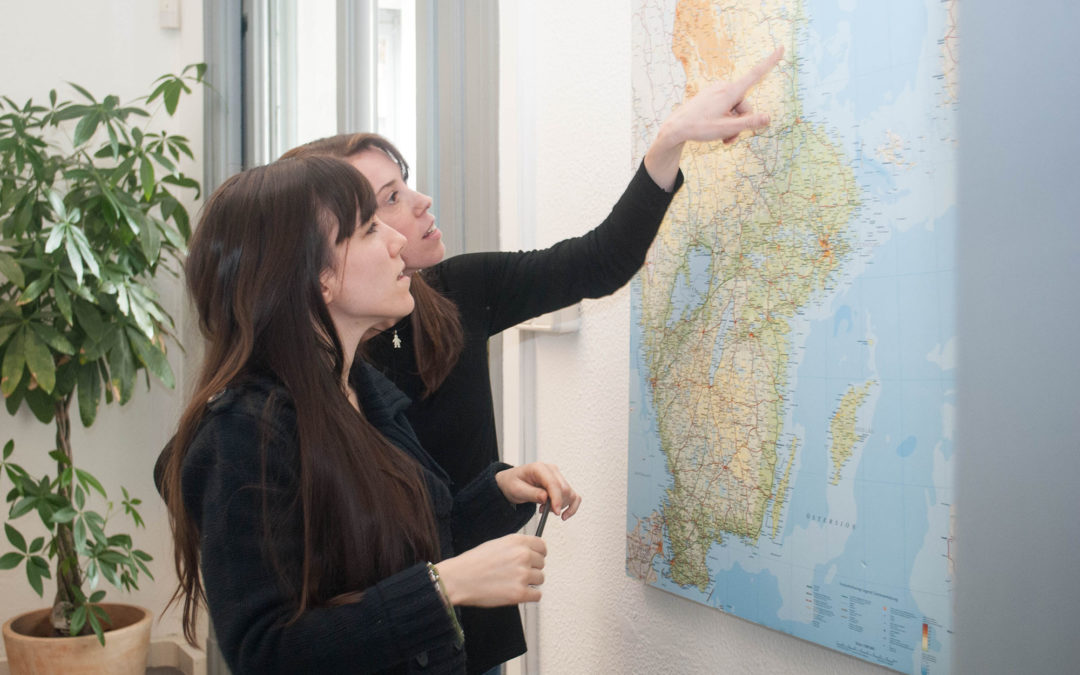 Two women pointing at a map of Scandinavia with a green plant in the back